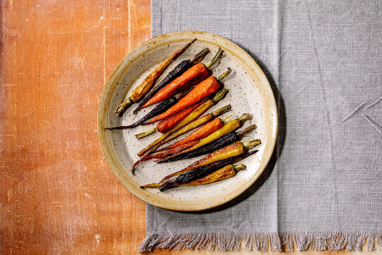 Grilled different colored carrots on ceramic plate