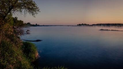Mglisty wschód słońca nad rzeką Wisłą z mostem w tle i parującą wodą w Annopolu w województwie Lubelskim