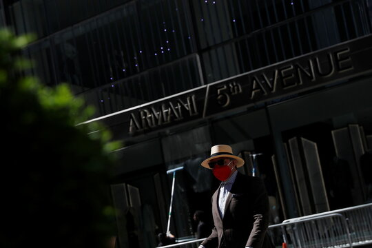 A man walks with a protective mask up 5th avenue in the Manhattan borough of New York City