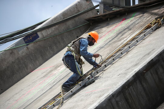 An employee works as part of the investigations at the site where an overpass for a metro partially collapsed with train cars on it, in Mexico City