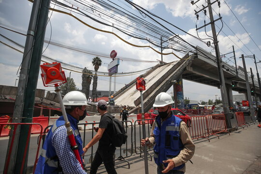 Employees work as part of the investigations in front of the site where an overpass for a metro partially collapsed with train cars on it, in Mexico City