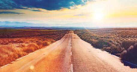 Obraz Carretera a través del desierto. Asfalto y viaje en coche con puesta de sol idílico . Concepto de viaje por carretera  y aventuras. - fototapety do salonu