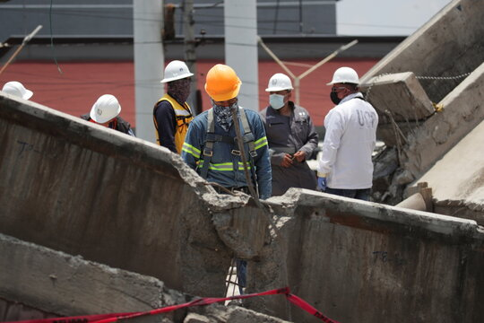 Employees work as part of the investigations at the site where an overpass for a metro partially collapsed with train cars on it, in Mexico City