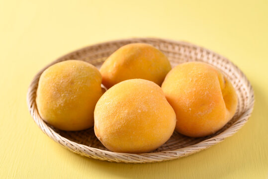 Yellow peaches in a bamboo basket on yellow background