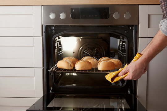 Crop male cooking buns at home