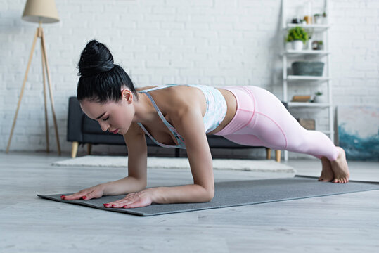 young brunette woman practicing forearm plank pose on yoga mat