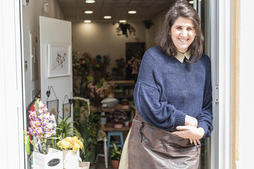 Obraz Portrait of a young cheerful woman working as florist standing at her own business shop entrance. Businesswoman concept. - fototapety do salonu