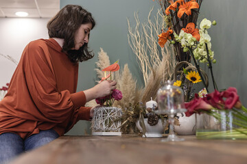 Obraz View of a young woman working as florist in her flower shop, sitting at wooden table and creating flower decoration, businesswoman concept. - fototapety do salonu