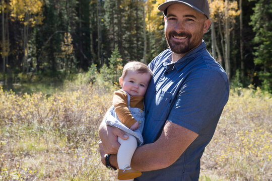 Portrait of a smiling man holding his baby daughter in the forest, California, USA