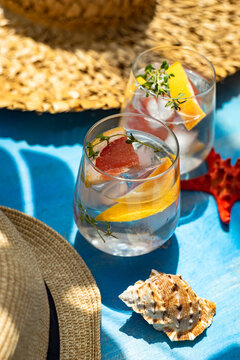Two glasses of ice water with grapefruit and thyme with straw hats, seashell and starfish ornaments