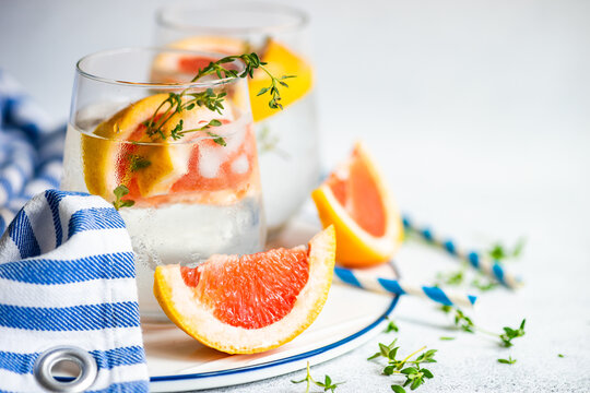 Two glasses of ice water with grapefruit and thyme