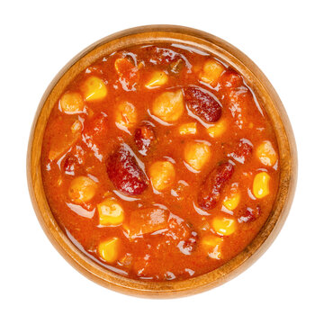 Vegetarian chili in a wooden bowl. Also chili sin carne, a spicy stew containing chili powder, tomatoes, kidney beans, chickpeas, onions, corn grains and spices. Close-up from above, macro food photo.