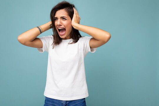 Portrait of emotional nervous young pretty nice brunette woman with sincere emotions wearing casual white t-shirt for mockup isolated on blue background with copy space and covering ears with hands