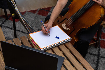 young man taking online cello lessons with his laptop on a wooden table and writing down in a notebook the explanations of the music teacher