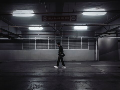 Rear View Of Man Standing On Illuminated Subway