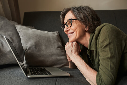 Woman wearing glasses looking at the laptop screen while texting with friends