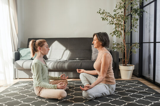 Woman meditating in front of her granddaughter and sitting on lotus pose