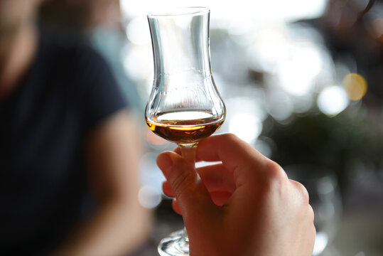 A glass with wiskey in hand of man with blurred background. Concept of whiskey tasting.