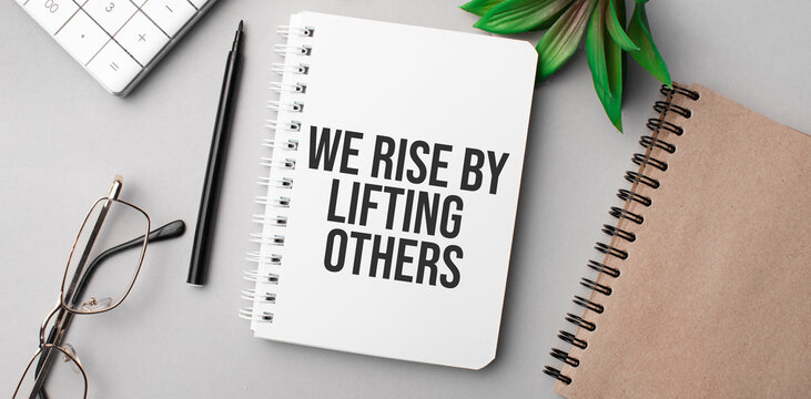 We Rise by Lifting Others is written in a white notebook with calculator, craft colored notepad, plant, black marker and glasses.