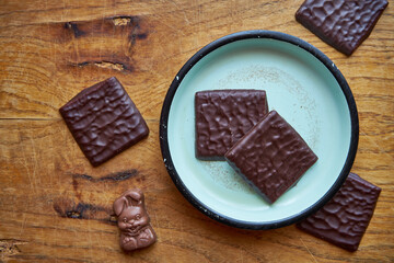 chocolate wafers stacked on a blue saucer and chocolate bunny on a wooden table, chocolate,...