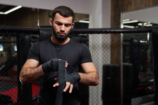 Mma caucasian fighter getting ready for fight, staying on boxing ring, copy space. Young male in black sportive outfit preparing, at gym alone. copy space
