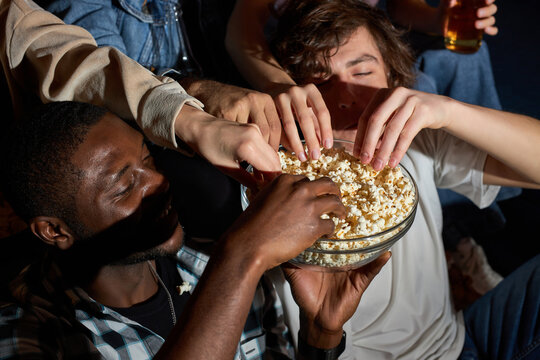Fun Movie with Friends. Group of people eating popcorn while watching movie on tv, at home, taking popcorn from bowl, enjoy weekends. close-up popcorn