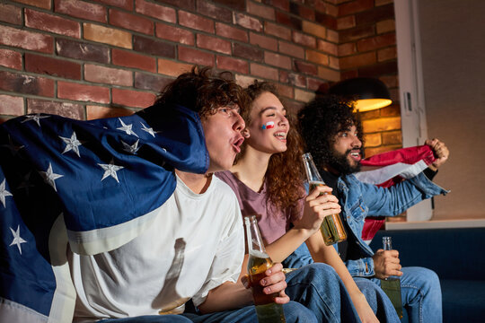 American friends drinking beer while cheering for favourite team on football championship on tv, young students screaming, yelling, celebrating victory