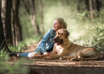Fototapeta Beste Freunde - ein Kind lehnt sich an seinen Hund, einen Broholmer, an und beide genießen in der Natur den Sonnenuntergang an einem Frühlingstag obraz