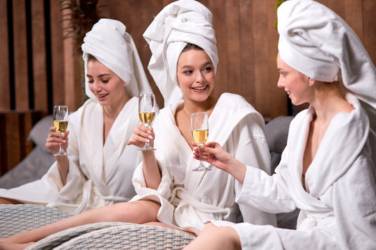 Women in bath towels communicating in spa salon while drinking champagne, spend holidays in wellness center together, before procedures