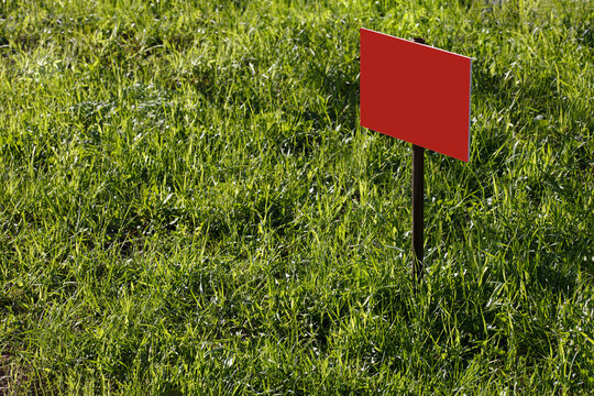 blank red sign mockup on green lawn background - close-up with selective focus