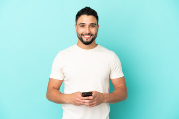 Young arab man isolated on blue background sending a message with the mobile - fototapety na wymiar