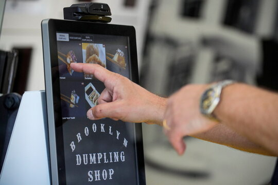 A customer places an order on a touch screen device at the Brooklyn Dumpling Shop in New York