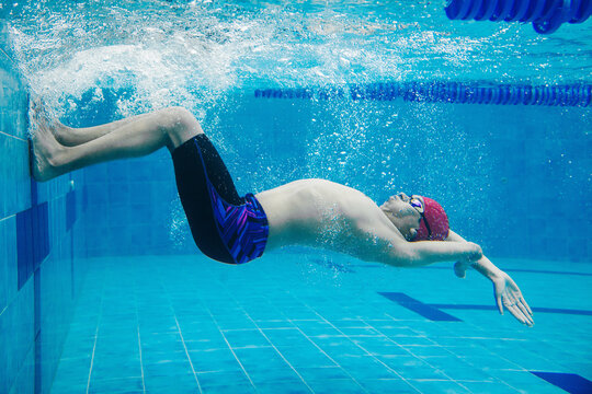 Paralympic Swimmer young latin man Underwater Training In Pool, disability concept