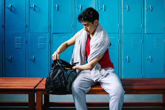 young latin disabled man Paralympic athlete with a towel in the locker room ay gym with hand hypoplasia in disability concept