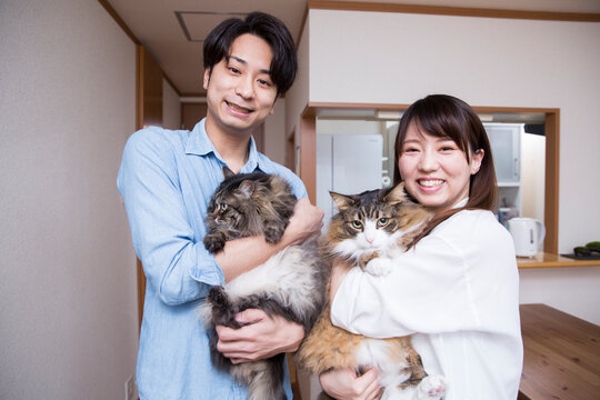 自宅でペットの猫を抱く日本人の若いカップル