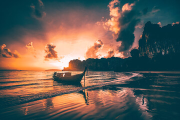 Amazing sunset with longtail boats silhouette at Railay beach, Thailand. - fototapety na wymiar