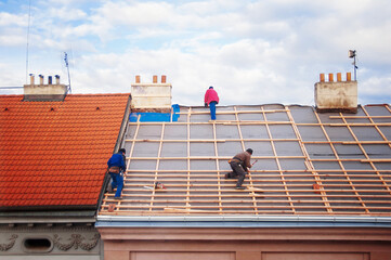 Fototapeta three builders replace the tiled roof in the old town obraz