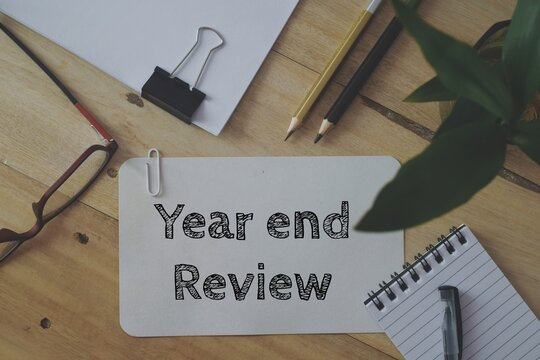 Year End Review business text memo written on a white card laid on wooden desk. Annual performance report submission concept, top view.