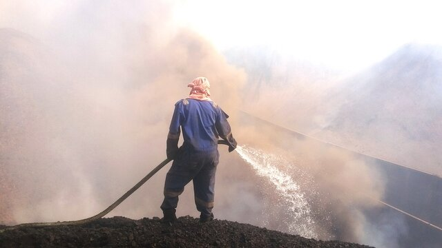 Rear View Of A Man Standing Against A Burnt Coal Try To Extinguishing It