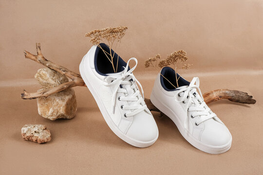 Ethical vegan shoes concept. A pair of white sneakers with dry flowers on the wood and pile of stones, neutral beige craft paper background