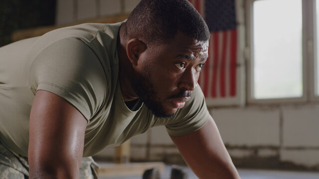 Black soldier doing push ups in gym