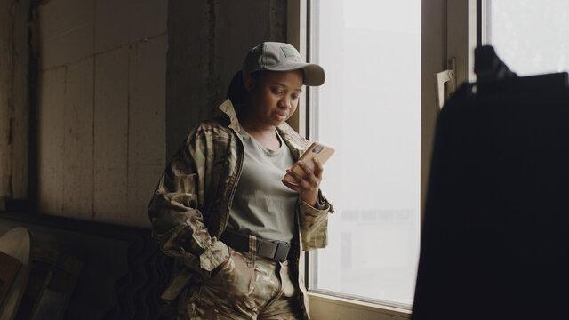 African American female soldier using smartphone near window