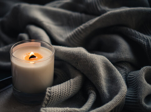 Burning candle in glass with wooden wick, handmade natural wax candle with knitted blanket