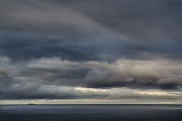 Ujęcie szarego zachmurzonego nieba nad morzem oraz samotnego statku pod nimi