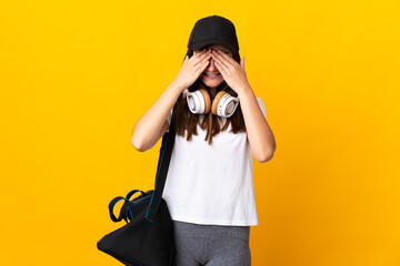 Young sport woman with sport bag isolated on yellow background covering eyes by hands