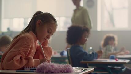 Fototapeta Girl writing test in classroom. Smart student making notes in exercise book  obraz