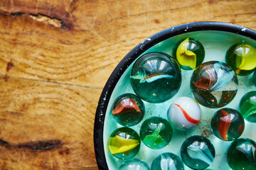 Obraz colored glass balls for play arranged on a saucer which is on a wooden table, glass balls, balls for games, game, fun, entertainment, hobby, abstract - fototapety do salonu