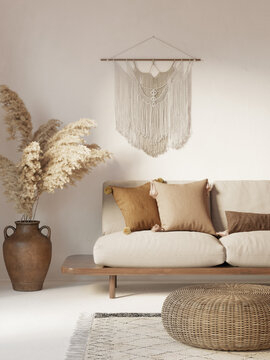 3d white and beige bohemian interior with boho macrame wall hanging decor, pampas grass, a round wicker coffee table and a sofa with cushions with pom pons