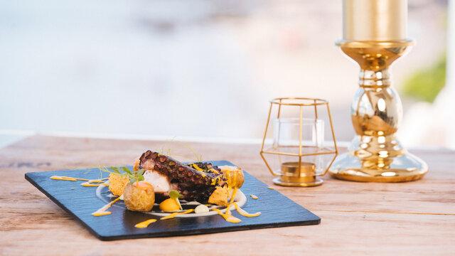 Plato de pulpo cocinado al grill y puré de  patatas sobre sonfo de madera y vela dorada