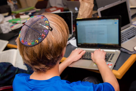 Young Jewish boy wearing yarmulke from the back typing on a keyboard at school.